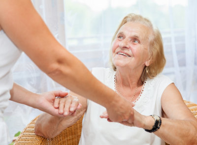 elderly woman holding a hand of a woman