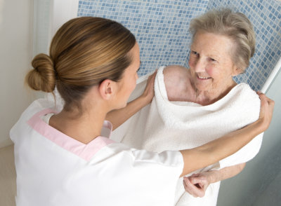 therapist assisting elderly woman for shower